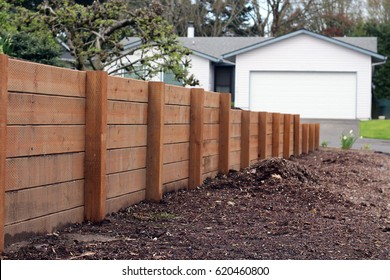 Retaining wall from one persons house to the other, dividing the two yards. Made of pressurized wood, very sturdy and strong