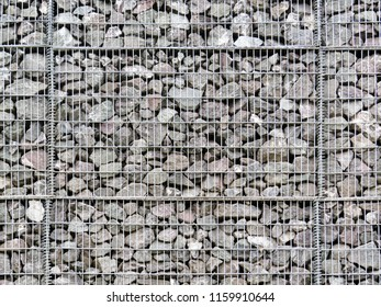 Retaining wall of stone rocks hold by a metal net