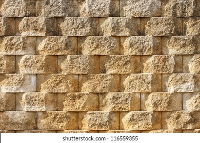 A retaining wall of textured interlocking blocks in early morning light
