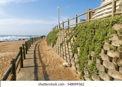 Retaining wall and wooden barrier on  empty beach against blue skyline and residential buildings on beach in Ballito near Durban, South Africa