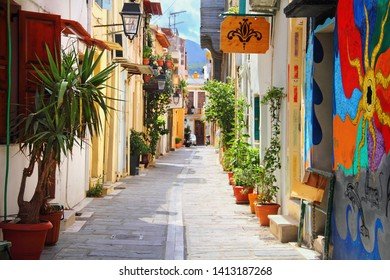 RETHIMNO, GREECE - SEP 06, 2018: Cozy city street full of plants in a clay pots and colorful painting on the house wall in old quarter of Rethymno, island of Crete, Southern Greece, Europe.