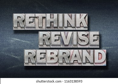 rethink revise rebrand words made from metallic letterpress on dark jeans background