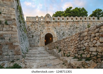 Rethymno, Crete, Greece, 10.02.2018. Fortezza fortress in Rethymno on Paliokastro hill. Old stonework, arched entrance to the fortress lit by lanterns, beautiful sunset sky