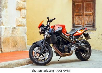 Rethymno, Greece - May 3, 2016: Sport motorbike parked on narrow touristic street. Resort town Rethymno in Greece. Mediterranean architecture on island Crete