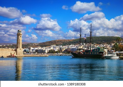 Rethymno (Rethimno), Crete island, Southern Greece, Europe. Beautiful old town, ancient Lighthouse, Venetian Harbor with old sailing ship reflected in the water, city houses and blue cloudy sky