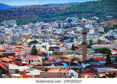 Rethymno (Rethimno), Crete island, Southern Greece, Europe. Beautiful city view, traditional greek houses under red tile and minaret of old turkish mosque at the background of mountain slope