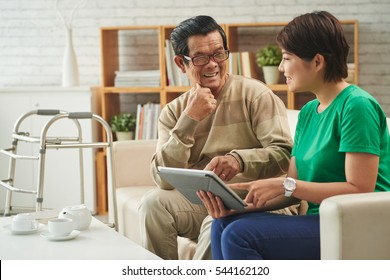 Retired Asian man and young woman watching photos on tablet computer