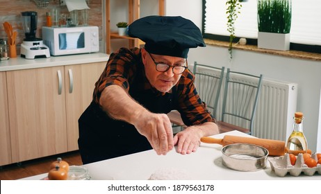 Retired baker man sieving flour on chopping board making dough at home. Elderly senior chef with bonete and uniform sprinkling, sifting, spreading ingredients by hand, baking homemade pizza and bread