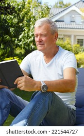 Retired businessman sitting at garden and working on digital tablet.
