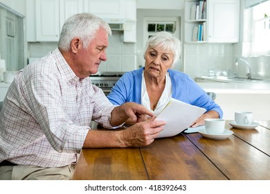 Retired couple discussing with documents while sitting at table in home