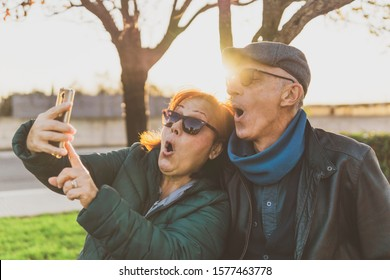 retired couple enjoying free time taking funny selfie - middle-aged couple having fun together using smartphone - happy mature people take photos with mobile phone - sunny warm filter