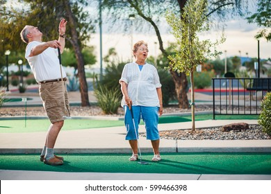 retired couple having fun playing mini golf