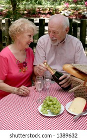 A retired couple having a picnic in the park.  The husband is opening the wine.