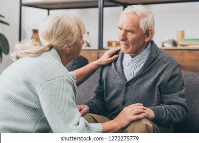 retired couple holding hands and looking at each other at home