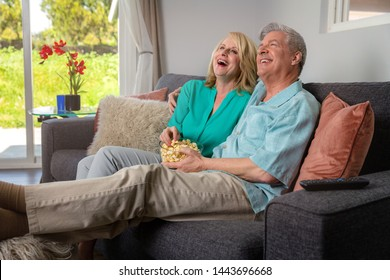 Retired couple laughing at comedy movie, TV, enjoying leisure time together, laughing on sofa with popcorn