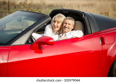 retired couple in red cabriolet going on vacation