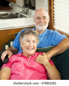 Retired couple relaxes and watches television in their motor home.
