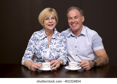 retired couple sitting by the table having coffee dark background