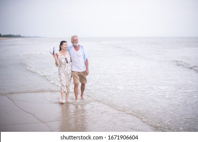 Retired couple walking on the beach.happy senior man and woman  holding hands together with love and care in romantic mood.Positive relationship of old people concept