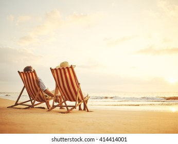 Retired couple watching sunset in vintage beach chairs