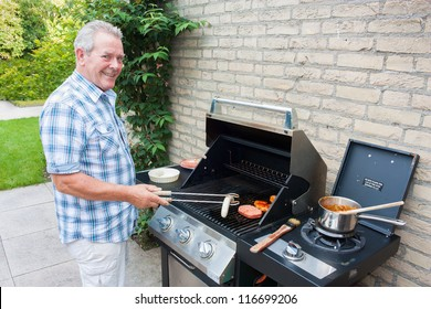Retired dutch senior man grilling meat in his back yard on a summer day