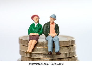 Retired / elderly couple sitting on euro coins