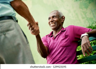 retired elderly people and free time, happy senior african american and caucasian male friends greeting and sitting on bench in park