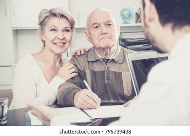 Retired father and mature daughter in social department with social employee