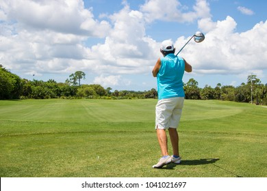 Retired female golfer hitting a ball on a beautiful golf course