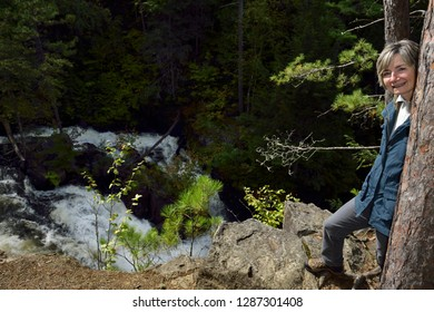 Retired female hiker standing on the precipice of the Eau Claire Gorge water falls
