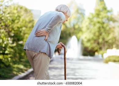 Retired ill woman feeling backache in the park