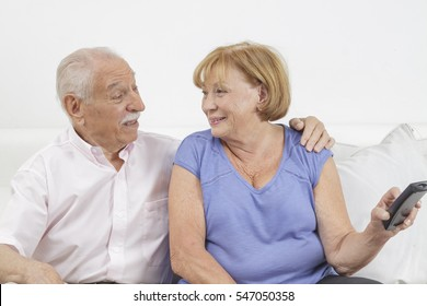 Retired loving husband and wife watching television at home together and having fun