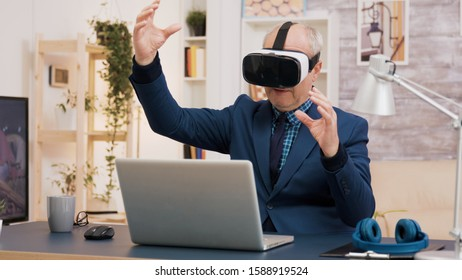 Retired man experiencing virtual reality using vr headset in living room. Cup of coffee on the table.