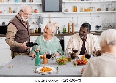 retired man in eyeglasses pouring red wine in glass near happy interracial friends