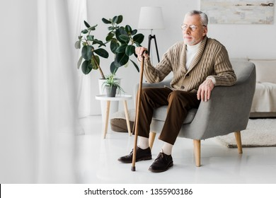 retired man in glasses sitting in armchair with walking cane