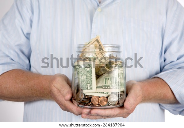 Retired man holding his retirement piggy bank money account in his hands in a glass jar.