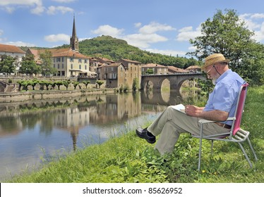 Retired man painting by bank of river in rural france.  Saint-antonin-noble-val, midi-pyrenees, southern france