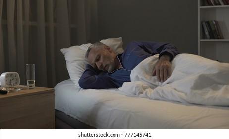 Retired man seeing nightmares in his dreams, sleeping in ward of nursing home