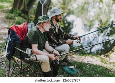 Retired man sitting in the folding chair while fishing with his son