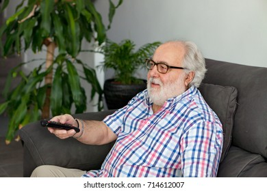 Retired man with white beard watching TV on the couch of his house