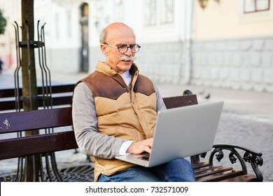 Retired man working on his laptop in the bench city street