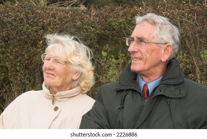 Retired married couple sitting outside on a bright sunny autumn / fall / winter day and looking at something to the side of them