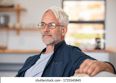 Retired mature man sitting on couch wearing spectacles and thinking. Smiling old man planning the retirement. Thoughtful senior business man relaxing at home while looking away with copy space.