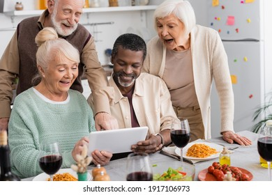 retired multicultural people looking at digital tablet with happy senior friends near tasty food on table