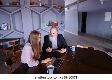 Retired old men interested in how to correctly use online application with help of laptop technology and communicates with female social worker. Beautiful stately gray head man with long beard dressed