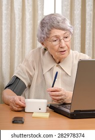 Retired old woman has just sent her blood pressure and pulse information to telemedicine center. At now, she is waiting answer from her physician opposite laptop monitor. Vertical shot.