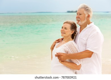 Retired senior Caucasian couple wearing white casual clothes together on peaceful summer travel resort beach