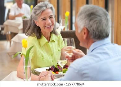 Retired senior couple enjoying meal at table in restaurant