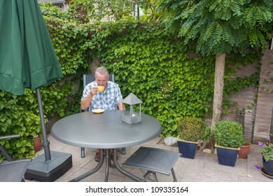 Retired senior Dutch man in deep thoughts whilst drinking a cup of hot coffee  in his back yard