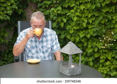 Retired senior Dutch man in deep thoughts drinking a cup of hot coffee in his back yard